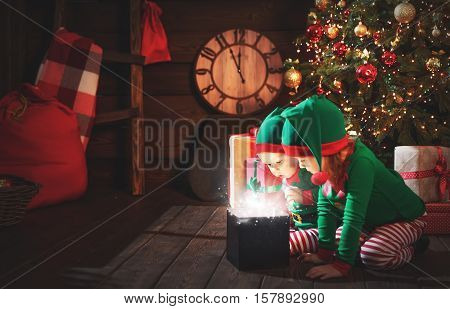 happy children brother and sister elf helper of Santa with a Christmas magic gifts