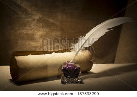 Literature concept. Old inkstand with feather near scroll on canvas background.