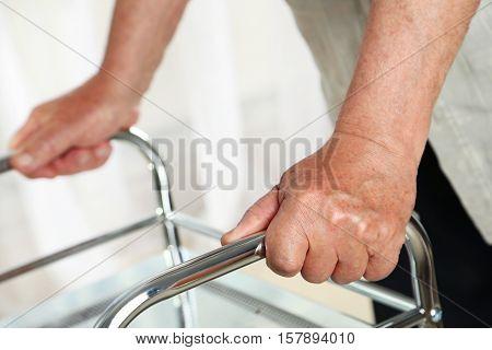 Senior hands holding on a walker, close up