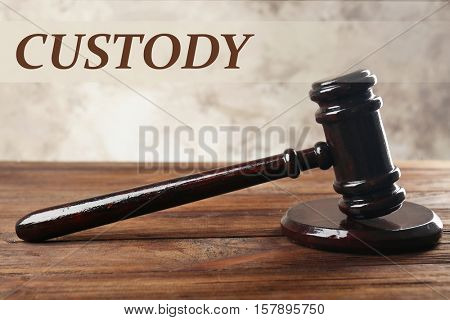 Wooden judge's gavel on table, closeup. Word CUSTODY on background