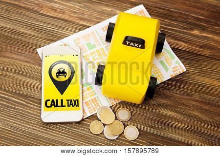 Yellow toy taxi cab, smartphone, coins and map on wooden background. Taxi service application on phone screen.