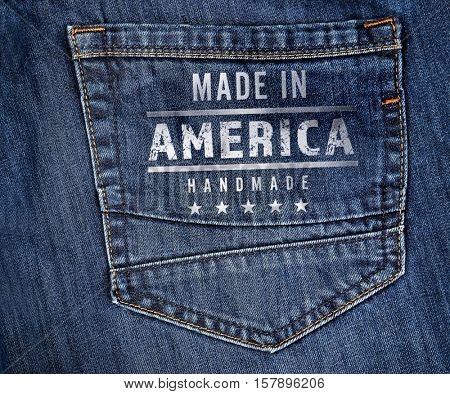 Printed text MADE IN AMERICA HANDMADE on jeans pocket, closeup. Manufacturing quality concept.