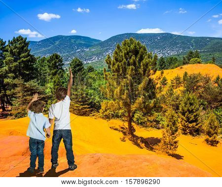 Orange and red picturesque hills in Languedoc - Roussillon. Two boys - brothers of seven and four years admire the magnificent nature