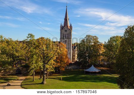 Autumn park with old medieval church in Cesis town, Latvia
