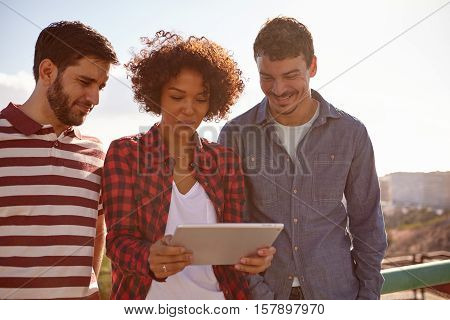 Three Smiling Friends Focusing On Tablet