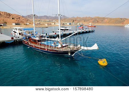 SHARM EL SHEIKH EGYPT - DECEMBER 4: The sail yacht with tourists is near pier in harbor of Sharm el Sheikh. It is popular tourists destination on December 4 2013 in Sharm el Sheikh Egypt