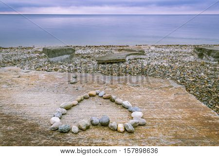 Heart made of stones and lake - Image on the shore of the lake Bodensee south Germany with a heart made of stones and the beautiful blue lake and sky at the horizon
