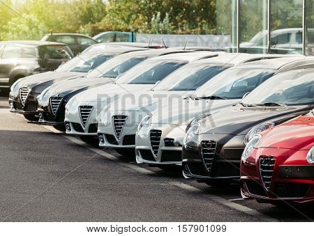 Generic Brand new cars in a row waiting for their customers - modern beautiful car dealership for sale.