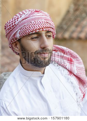 Young smiling handsome arabian man wearing traditional clothes