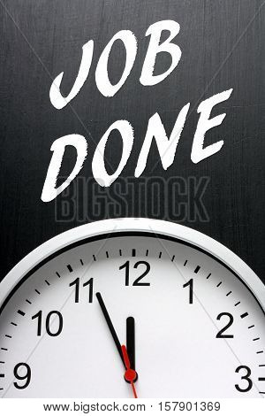 The words Job Done in white text on a blackboard above a modern clock with the time at almost midnight or twelve noon