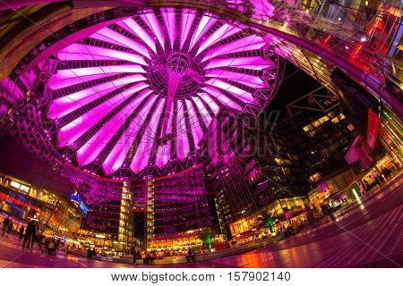Berlin, Potsdamer Platz, May 13th 2016: People having a walk under the changing colours of the modern dome.