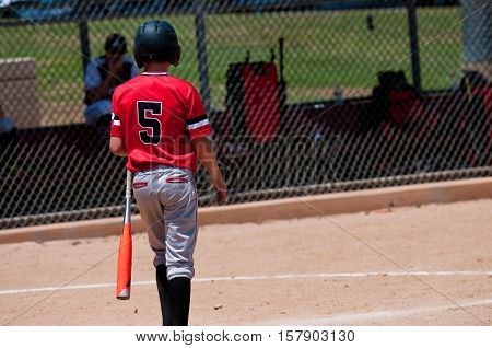 Rear view of american baseball boy going up to bat.