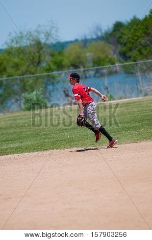 American youth baseball player running on the field.