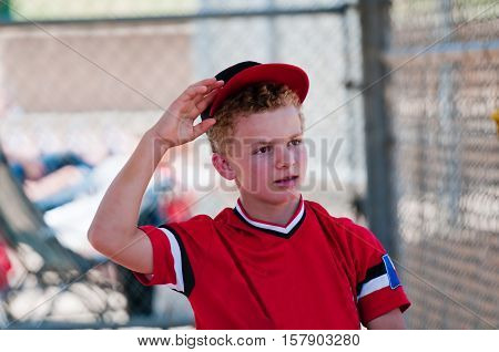 Teenage baseball boy in dugout reaching for ball cap.