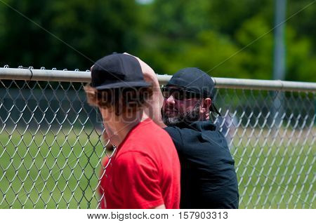 Teen boy and middle-aged father leaning on a fence during a baseball game.