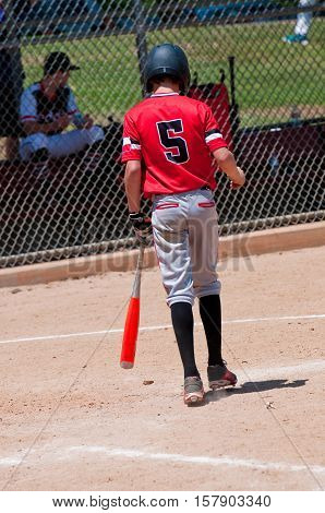 Rear view of american youth baseball boy going up to bat.