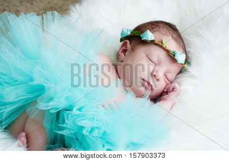 Portrait of adorable newborn baby girl in teal tutu sleeping on white fur.