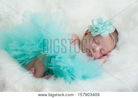 Precious baby girl in teal outfit laying on white fur.
