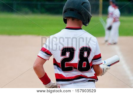 American teenage baseball player looking down at bat.