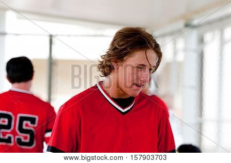 Closeup of baseball player with long hair smiling in dugout.