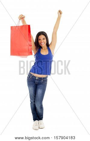 young happy and beautiful hispanic woman holding red shopping bag smiling excited isolated on white background in shopaholic fashion sales and consumerism concept