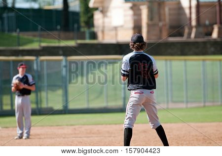 American baseball teenage pitcher in black and grey jersey on the mound during a game. Looking away from camera.