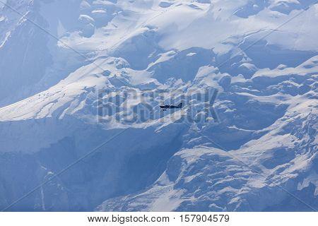Small plane flying by Mt Blanc. Chamonix Auvergne-Rhone-Alpes France.
