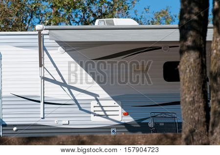 RV travel trailer camper parked under a tree outdoors.