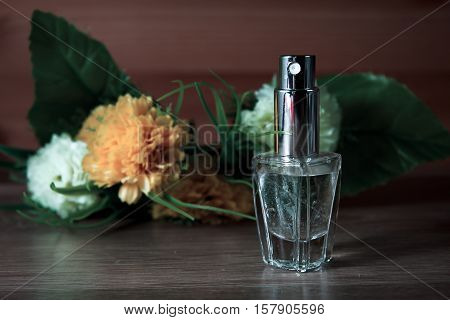 female perfume and flowers in wooden background
