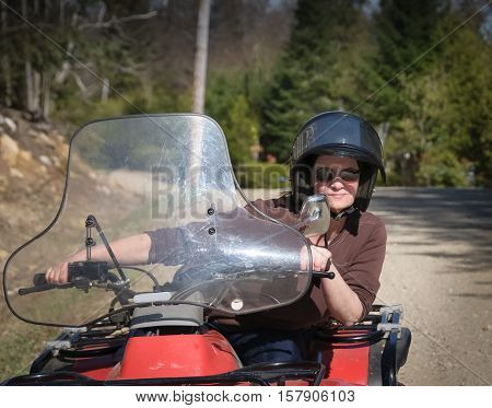 young woman riding a Quad in Quebec rural road Canada