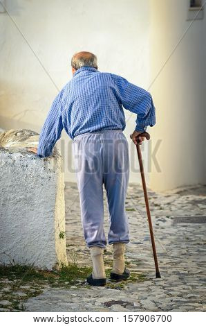 Old tired man with a walking stick shooted from behind elderly concept