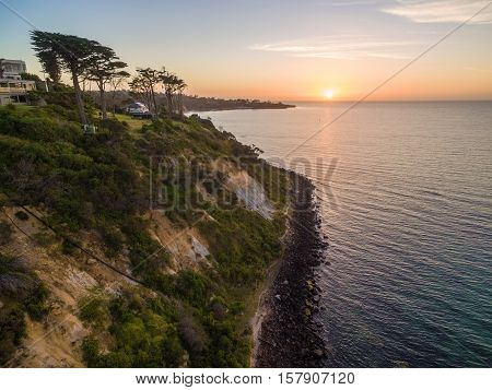 Beautiful Trees On A Green Hill Near The Ocean At Sunset.