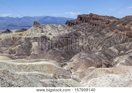 Zabriskie Point in Death Valley under blue sky