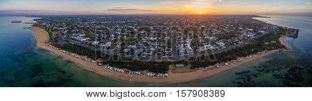 Aerial Panorama Of Sunrise Over Brighton Suburb, Showing Iconic Beach Huts, Houses, And The Ocean. M