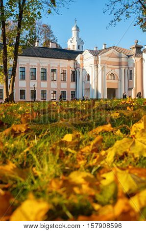 VELIKY NOVGOROD RUSSIA-OCTOBER 9 2016. Veliky Novgorod Kremlin park with Clock Tower of St Sophia Cathedral and fallen maple autumn leaves on the foreground. Focus at the clock tower
