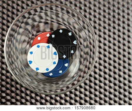 Poker chips in a Martini glass on a black background