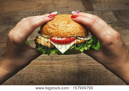 Eating hamburger. Delicious hamburger in the hands. Fastfood meal. Vintage toned
