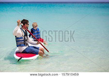 family of two enjoying stand up paddleboarding at caribbean vacation active and healthy lifestyle