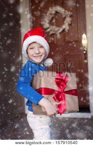 little boy in santa's hat holding christmas gift enjoying snowy christmas time