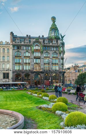 ST PETERSBURG RUSSIA - OCTOBER 3 2016. Zinger House on Nevsky Prospect and Kazan square with people walking along in autumn evening in St Petersburg center Russia. Architecture city scene