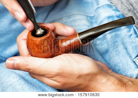 Man Holding Smoking Pipe In Hand And Tamping Down Tobacco