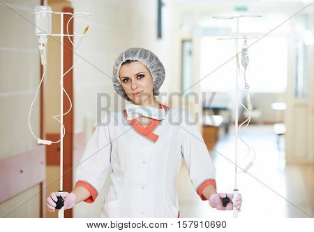 Young medic nurse with droppers in hospital