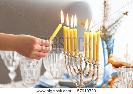 Female hand lighting candles in menorah on table served for Hanukkah