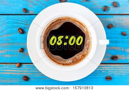 Nine hours or 8:00 on morning cup of coffee like a round clock face. Top view.