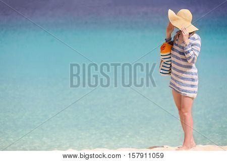 woman in sunhat and beach cover enjoying perfect caribbean beach copyspace on side