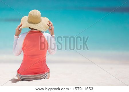 woman in sunhat and rashguard enjoying perfect caribbean beach sun protection concept with copyspace