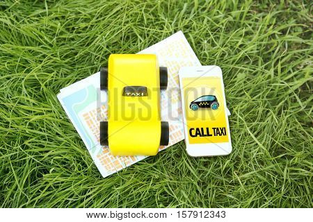 Yellow toy taxi cab, smartphone and map on green grass background. Taxi service application on phone screen.