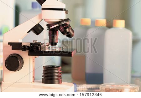Microscope in the laboratory against the reagent bottles. Toned Image
