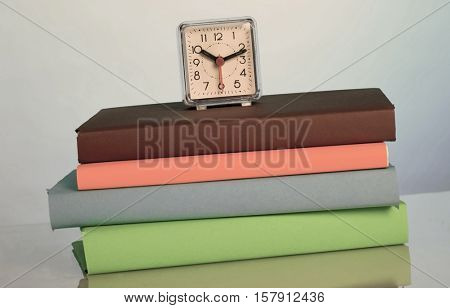 Alarm clock and color books. Toned Image