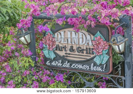 OLINDA, BRAZIL, JANUARY - 2016 - Detail view of crafted decorated restaurant banner post surrounded by flowers at Olinda town Pernambuco Brazil